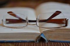 Glazen op boekpagina Stock Fotografie