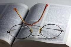 Glazen op de bijbel Stock Foto's