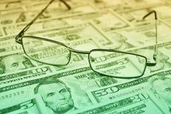 Glazen op dollargeld, financiële en bedrijfsconcept stock afbeeldingen