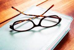 Glazen op een boek stock afbeelding