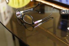 Glazen op een bureau in het bureau Glazen op een transparant bureau in het bureau Stock Afbeeldingen