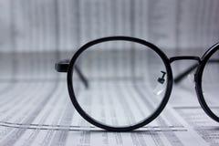 Glazen op financiële krant onder licht tintblauw royalty-vrije stock fotografie
