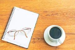 Glazen op kop van de notitieboekje de witte koffie en houten lijstachtergrond Stock Afbeeldingen