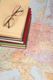 Glazen op stapel van boeken op kaart royalty-vrije stock afbeelding