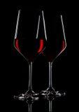 Glazen rode wijn met bezinning over zwarte Stock Fotografie