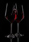 Glazen rode wijn met bezinning over zwarte Stock Foto's