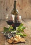 Glazen rode wijn met kaas, crackers en druif Stock Afbeeldingen
