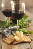 Glazen rode wijn met kaas, crackers en druif Stock Foto's