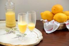 Glazen van crema Di limoncello, fles en citroenen Stock Afbeeldingen