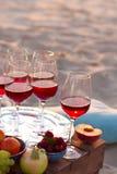 Glazen van de rode wijn op het zonsondergangstrand Royalty-vrije Stock Afbeelding