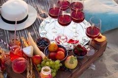 Glazen van de rode wijn op het zonsondergangstrand Stock Foto