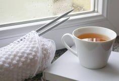 Glazen venster met regendalingen en thee in de mok, het witte wollen breien en boek op de vensterbank stock foto