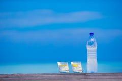Glazen wateren met citroen en fles op houten Royalty-vrije Stock Foto