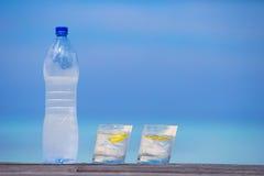 Glazen wateren met citroen en fles op houten Stock Foto