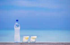 Glazen wateren met citroen en fles op houten Royalty-vrije Stock Afbeelding