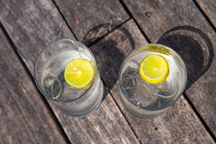 Glazen wateren met citroen op houten Royalty-vrije Stock Foto's