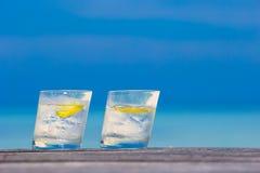 Glazen wateren met citroen op houten op overzees Stock Afbeeldingen