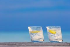 Glazen wateren met citroen op houten op overzees Stock Foto's