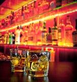 Glazen whisky met ijs op barlijst dichtbij whiskyfles op warme atmosfeer Stock Afbeelding