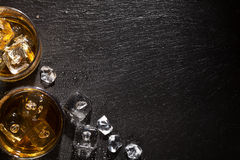 Glazen whisky met ijs op zwarte steenlijst royalty-vrije stock foto