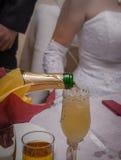 Glazen wijn in de handen van de bruid en de bruidegom Royalty-vrije Stock Foto