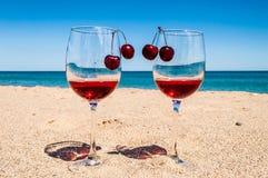 Glazen wijn en kersen dichtbij het overzees Royalty-vrije Stock Afbeeldingen