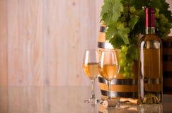 Glazen wijn met een fles een vat en druiven Stock Afbeeldingen