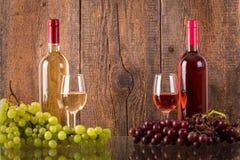 Glazen wijn met flessen en druiven Stock Afbeeldingen