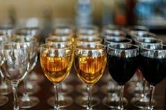 Glazen witte wijn en rode wijnflessenachtergrond op de lijst Stock Afbeeldingen