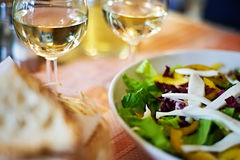 Glazen witte wijn en salade op lijstkoffie Stock Afbeeldingen