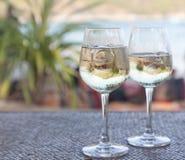 Glazen witte wijn met ijs op een lijst bij de strandkoffie Stock Afbeelding