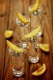 Glazen wodka met citroen op houten achtergrond Royalty-vrije Stock Foto's