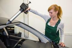 Glazenmaker die met toepassingskanon kleefstof aanvragen windschermvervanging stock foto's
