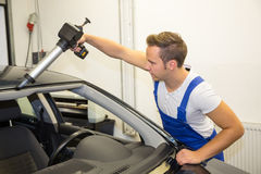 Glazier with application gun in garage replacing windshield or windscreen Royalty Free Stock Photos