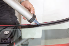 Glazier applying rubber sealing to windscreen Stock Photography