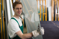 Glazier handling piece of glass in workshop Stock Photos