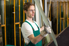 Glazier handling piece of glass in workshop Royalty Free Stock Photos