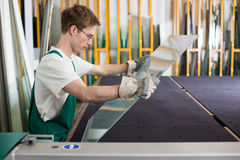 Glazier handling piece of glass in workshop Royalty Free Stock Image
