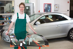 Glazier handling windscreen in garage Stock Photography