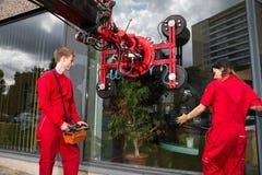 Glazier operating glass installation crane Royalty Free Stock Photography
