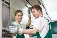 Glazier putting glass in grinding machine Stock Photo