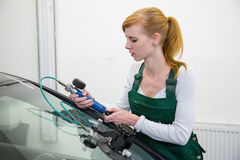 Glazier repairing stone-chipping damage on car's windshield Royalty Free Stock Photos