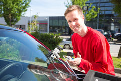Glazier repairing windscreen after stone chipping damage Stock Photography