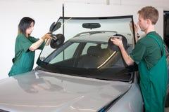 Glazier replacing windshield Stock Photo