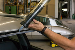 Glazier using application gun to apply adhesive for windscreen Stock Photo