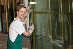 Glazier in workshop handling glass Stock Photo
