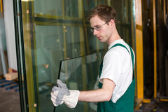 Glazier in workshop handling glass Stock Photos