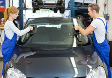 Glaziers replace windshield or windscreen on car after stone-chipping Royalty Free Stock Images