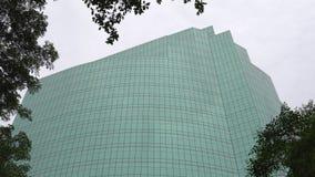 Glazige vensters van de moderne high-tech bouw over de groene boom bij daglicht stock footage