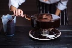 Glazing chocolate mousse cake, close-up Royalty Free Stock Photos